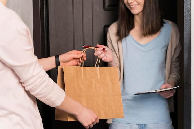 Vista frontal de la mujer entrega entrega mientras sostiene el bloc de notas y bolígrafo