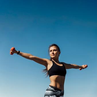 Vista frontal de la mujer entrenando con pesas