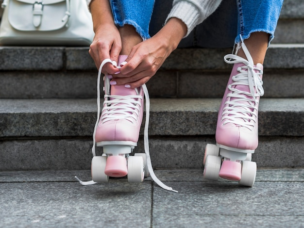 Vista frontal de la mujer en las escaleras atar cordones de los zapatos en patines