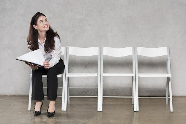 Vista frontal de la mujer esperando entrevista de trabajo con currículum