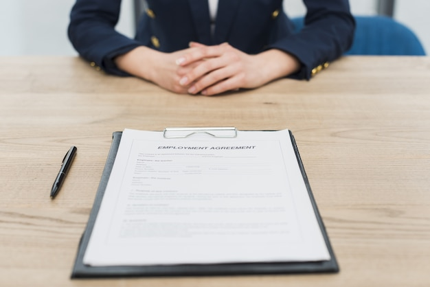 Vista frontal de la mujer esperando que firmes un nuevo contrato