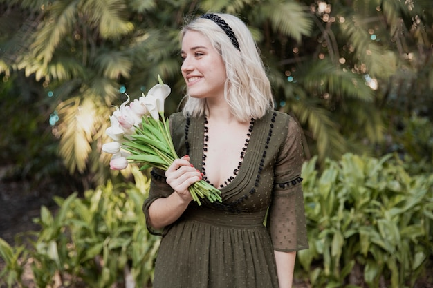Vista frontal de la mujer feliz posando mientras sostiene tulipanes