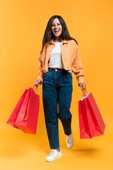 Vista frontal de la mujer feliz sosteniendo bolsas de la compra.