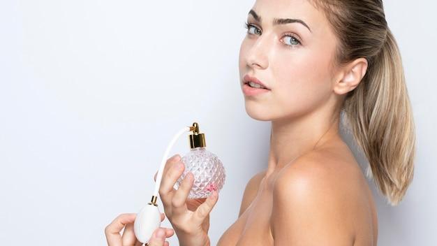 Vista frontal de la mujer con frasco de perfume
