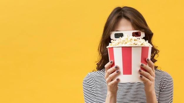 Vista frontal mujer con gafas 3d cubriendo su rostro con un cubo de palomitas de maíz