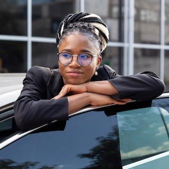 Vista frontal de la mujer con gafas descansando su cabeza sobre la puerta del coche