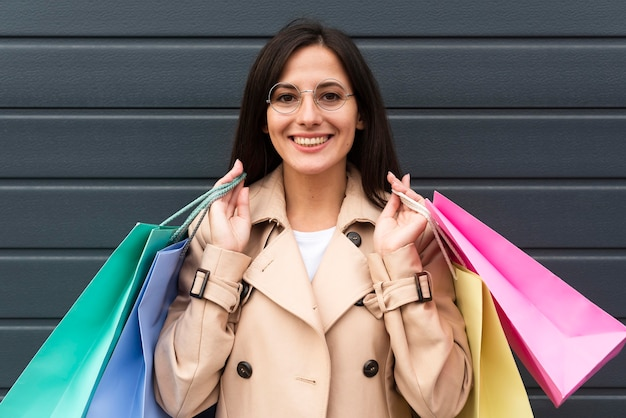 Vista frontal de la mujer con gafas sosteniendo un montón de bolsas de la compra.