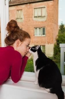 Vista frontal mujer y gato en el balcón