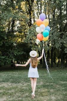 Vista frontal mujer con globos caminando