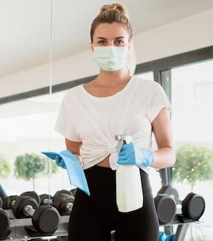 Vista frontal de la mujer con guantes desinfectando pesas en el gimnasio
