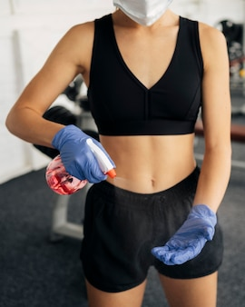 Vista frontal de la mujer con guantes y máscara médica en el gimnasio con desinfectante