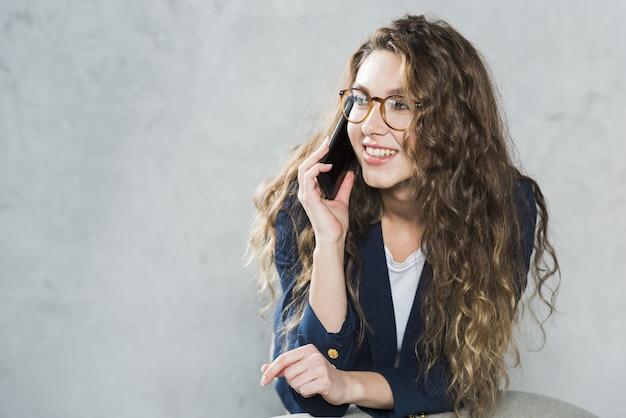 Vista frontal de la mujer hablando por teléfono mientras espera su entrevista de trabajo