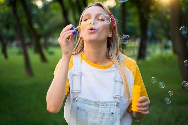 Vista frontal de la mujer haciendo burbujas al aire libre