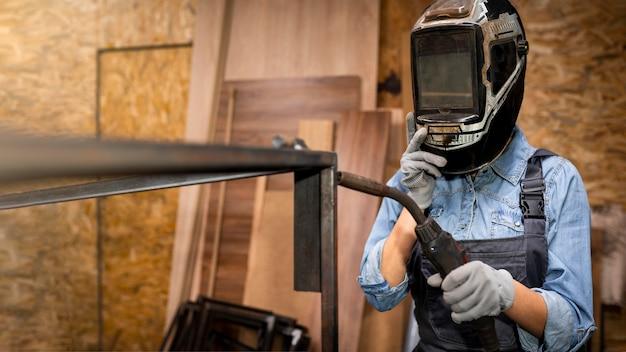 Vista frontal de la mujer con herramienta de soldadura y máscara