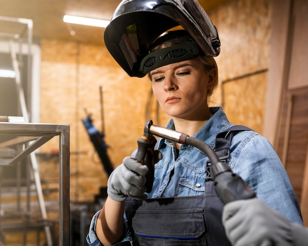 Vista frontal de la mujer con herramienta de soldadura