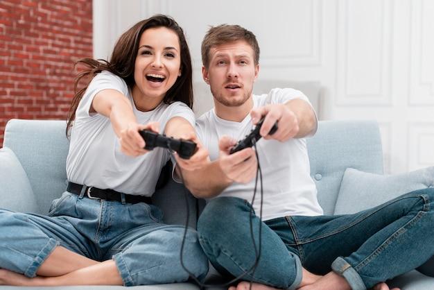 Vista frontal mujer y hombre divirtiéndose mientras juega con controladores