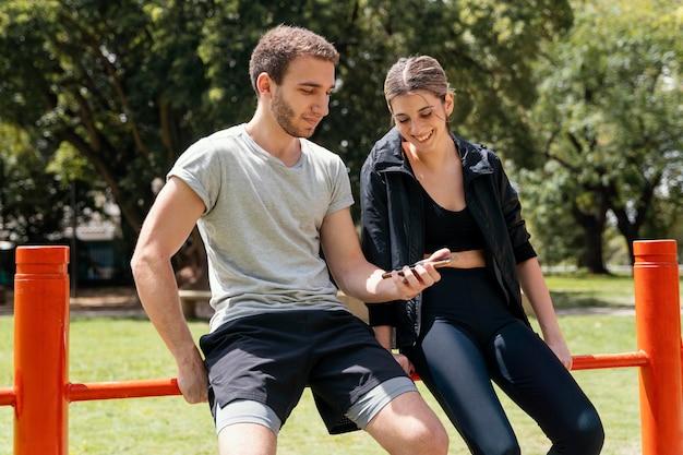 Vista frontal de la mujer y el hombre con smartphone al aire libre mientras hace ejercicio