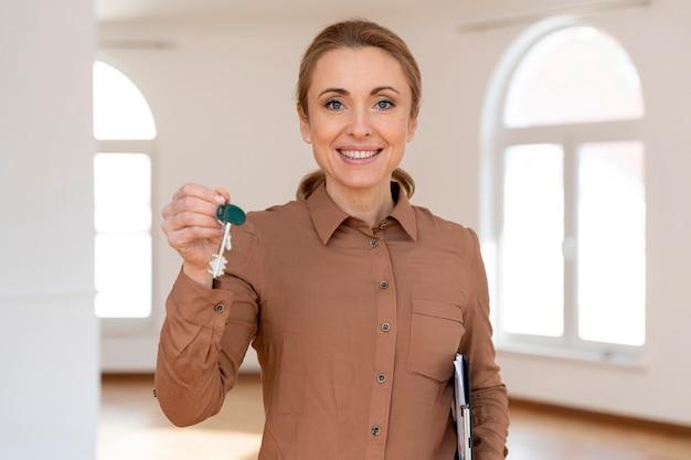 Vista frontal de la mujer inmobiliaria sonriente sosteniendo nuevas llaves de la casa