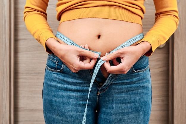 Vista frontal de una mujer irreconocible que mide la circunferencia de su cintura con una cinta métrica.