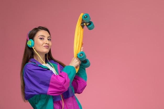 Vista frontal mujer joven en abrigo colorido con patineta en pared rosa, pose de mujer modelo mujer