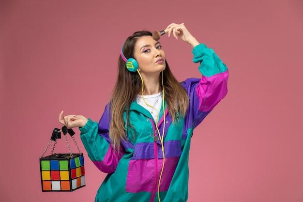 Vista frontal mujer joven en abrigo colorido sosteniendo bolsa y haciendo maquillaje en pared rosa, pose de mujer modelo de mujer