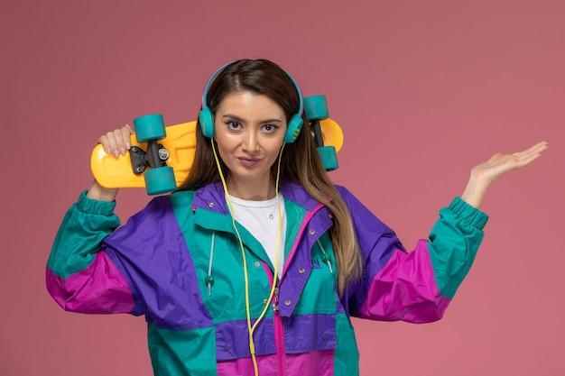 Vista frontal mujer joven en abrigo colorido sosteniendo patineta en pared rosa claro, pose de mujer modelo