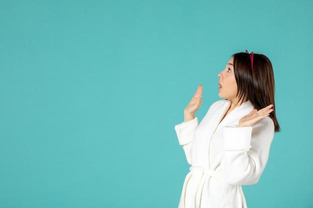 Vista frontal, de, mujer joven, en, bata de baño, en, pared azul