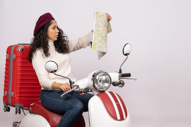 Vista frontal mujer joven en bicicleta observando mapa sobre fondo blanco ciudad color carretera vehículo de vacaciones velocidad de paseo en motocicleta