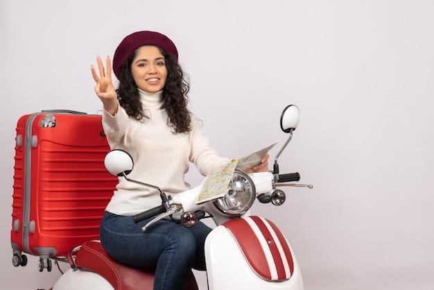 Vista frontal mujer joven en bicicleta sosteniendo mapa sonriendo sobre fondo blanco vuelo carretera motocicleta vehículo de vacaciones ciudad velocidad color