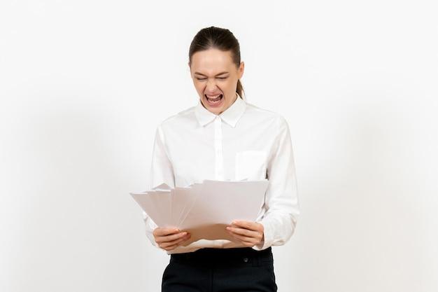 Vista frontal mujer joven en blusa blanca sosteniendo archivos sobre fondo blanco emociones femeninas sentimiento trabajo de oficina