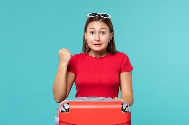 Vista frontal mujer joven con bolsa roja en espacio azul claro