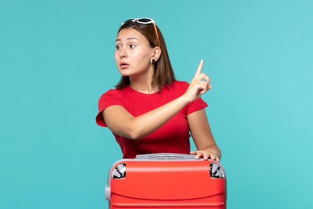 Vista frontal mujer joven con bolsa roja en el espacio azul
