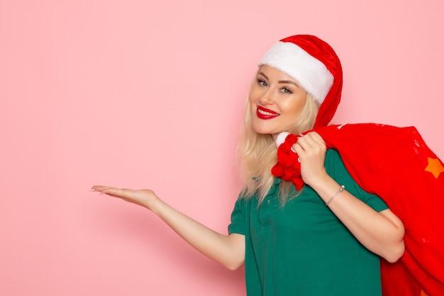 Vista frontal mujer joven con bolsa roja con regalos en la pared rosa modelo de vacaciones navidad año nuevo color