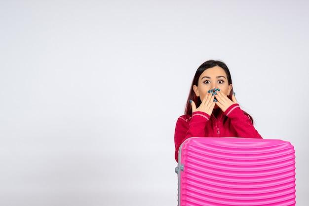 Vista frontal mujer joven con bolsa rosa sorprendida en la pared blanca emoción vacaciones mujer viaje viaje vuelo