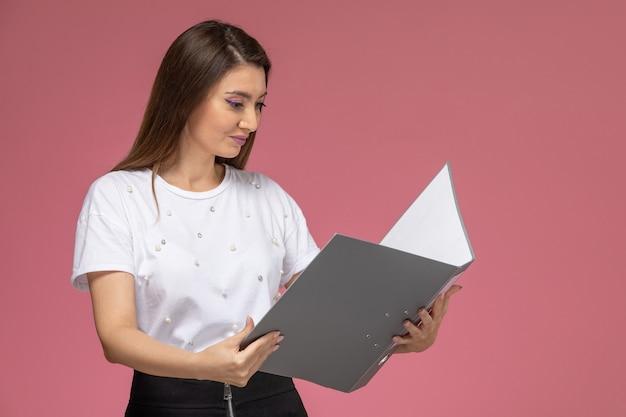 Vista frontal mujer joven en camisa blanca leyendo archivo gris en la pared rosa, mujer modelo