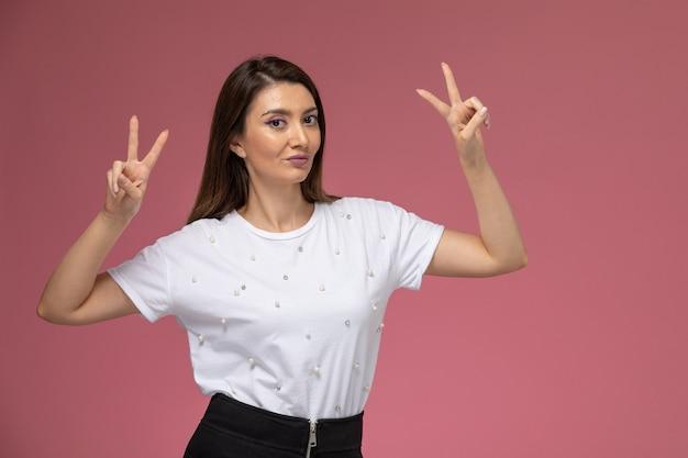 Vista frontal mujer joven con camisa blanca mostrando el signo de la victoria en la pared rosa, modelo de color pose de mujer