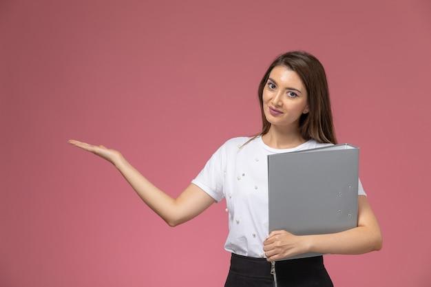 Vista frontal mujer joven con camisa blanca sosteniendo archivos grises en la pared rosa claro, pose de mujer modelo