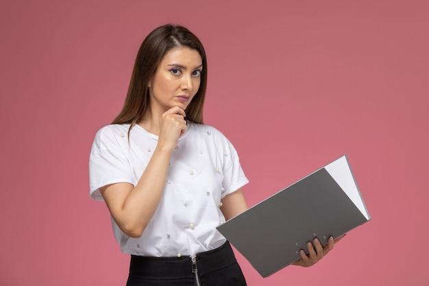 Vista frontal mujer joven en camisa blanca sosteniendo y leyendo un archivo gris en un escritorio rosa claro