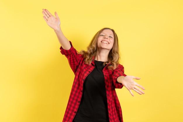 Vista frontal mujer joven en camisa a cuadros roja dando la bienvenida a alguien sobre fondo amarillo mujer emoción humana modelo moda chica