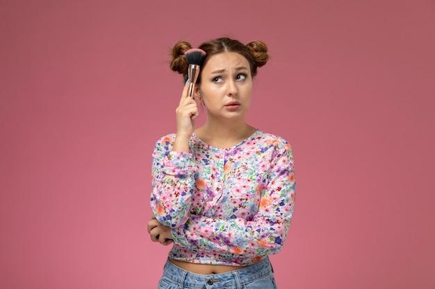 Vista frontal mujer joven en camisa de flor diseñada y jeans posando con pincel en la mano sobre el fondo rosa