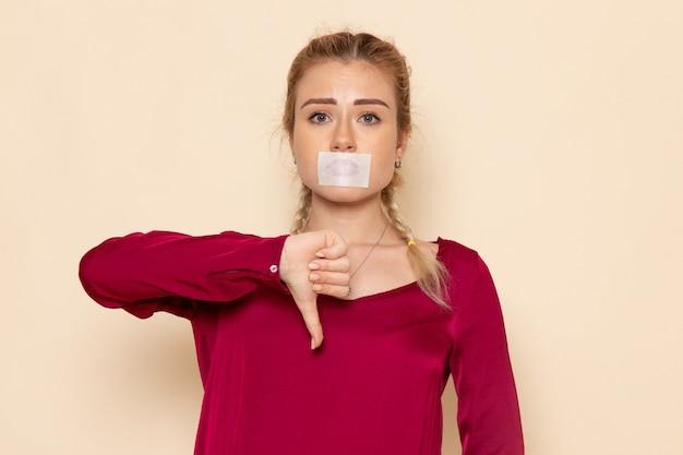 Vista frontal de una mujer joven en camisa roja con la boca atada en el espacio de la crema foto de tela femenina violencia doméstica