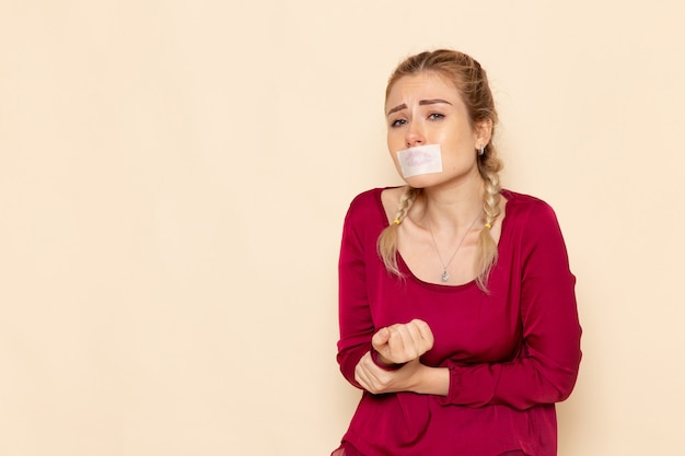 Vista frontal mujer joven en camisa roja con la boca atada llorando en el espacio de luz foto de tela femenina violencia