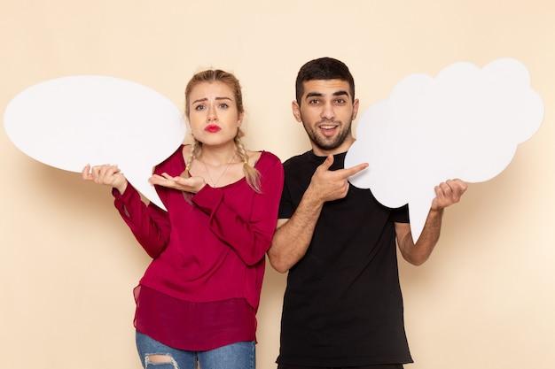 Vista frontal mujer joven en camisa roja junto con hombre sosteniendo carteles blancos en el espacio crema emoción fotográfica