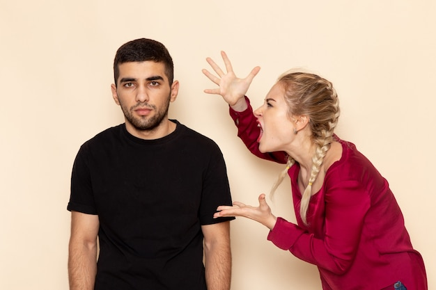 Vista frontal mujer joven en camisa roja peleando con el hombre en el espacio crema foto de tela femenina violencia