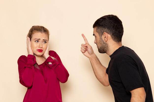 Vista frontal mujer joven con camisa roja sufre de amenazas físicas y violencia en el espacio crema foto de tela femenina violencia doméstica