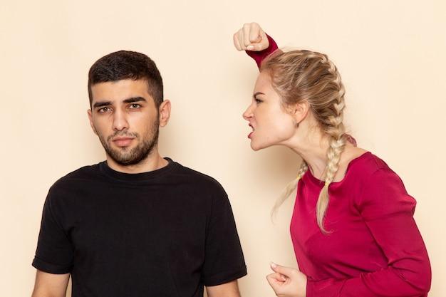 Vista frontal mujer joven en camisa roja tratando de golpear a un hombre en el espacio crema foto de tela femenina violencia doméstica