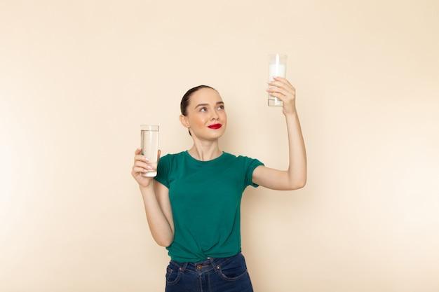 Vista frontal mujer joven en camisa verde oscuro y jeans con agua de leche sonriendo en beige