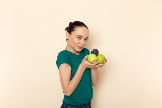 Vista frontal mujer joven en camisa verde oscuro y jeans con frutas en beige