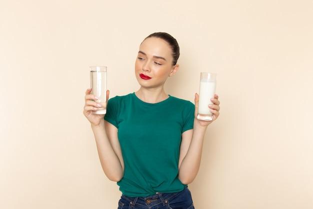 Vista frontal mujer joven en camisa verde oscuro y jeans con leche y agua en beige