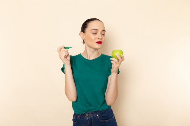 Vista frontal mujer joven en camisa verde oscuro y jeans con manzana e inyección en beige